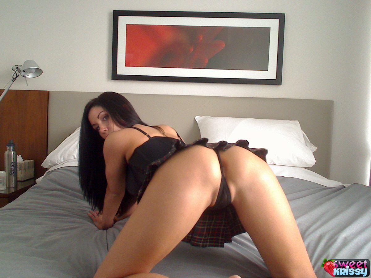 Сисястая брюнетка Sweet Krissy одета в черное и показывает свои ягодички на кровати