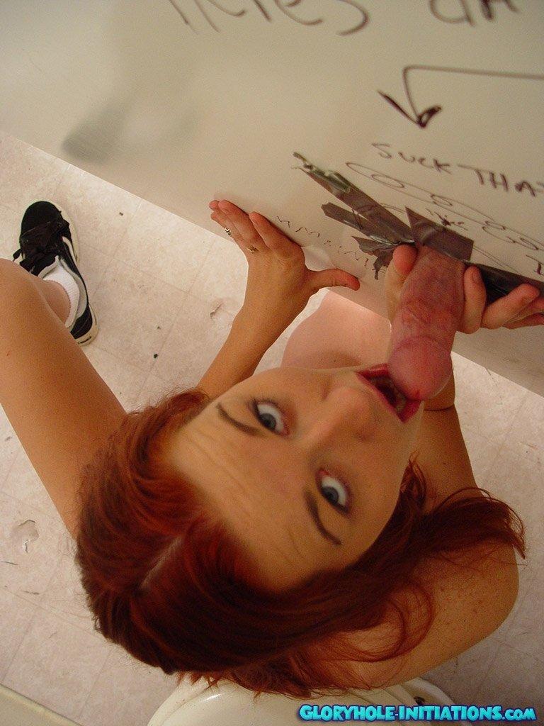 Рыжая деваха показывает свое тело в туалете и целует короткий член через стену кабинки.